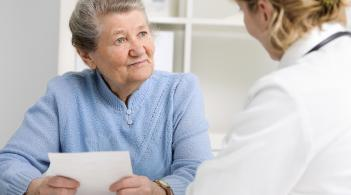 older woman sitting at a desk, holding a piece of paper, and talking to a healthcare provider