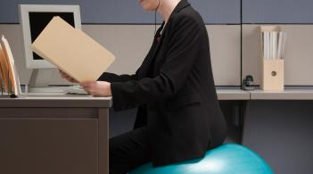 woman sitting on an exercise ball in front of her desk